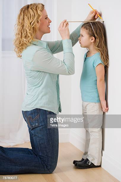 Mother marking daughter's height on wall