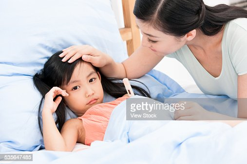 Mother measuring body temperature for young girl