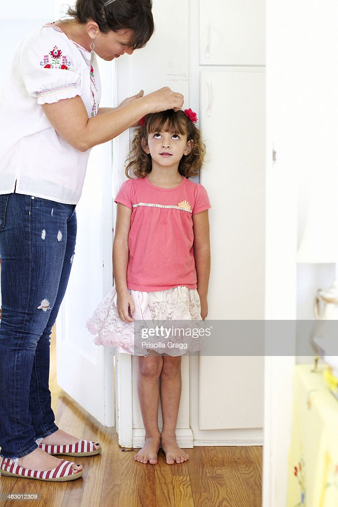 Mother measuring daughter's height : Stock Photo