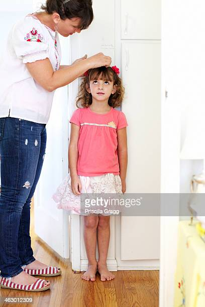 Mother measuring daughter's height