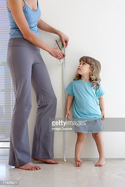 Mother measuring daughters height