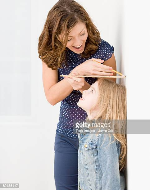 Mother measuring daughter?s height