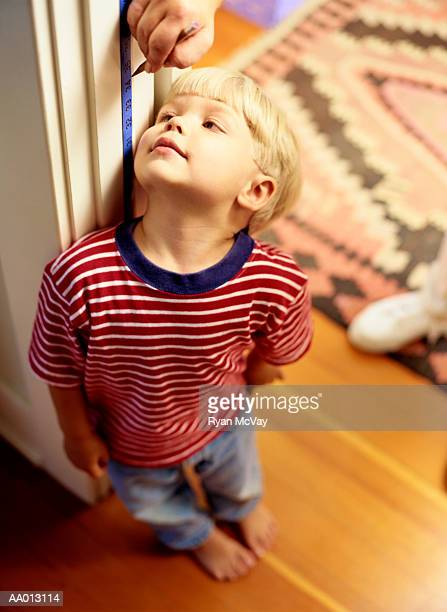 Mother measuring height of her son (3-5) in door frame