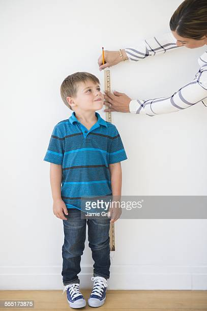 Mother measuring son (6-7) with ruler