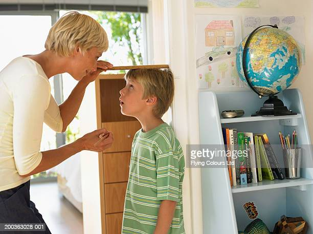Mother measuring son's (7-9) height against wall