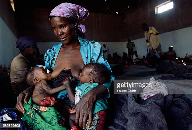 A mother nurses her malnourished son and an adopted child at a Medecins sans Frontieres therapeutic feeding center in Camacupa Angola where the...