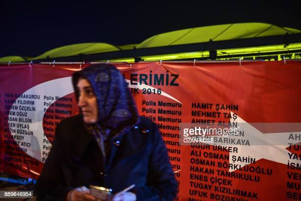 A mother of a victim stands in front of a banner with the victims' names during a cerenomy marking the first anniversary of the Vodaphone stadium...