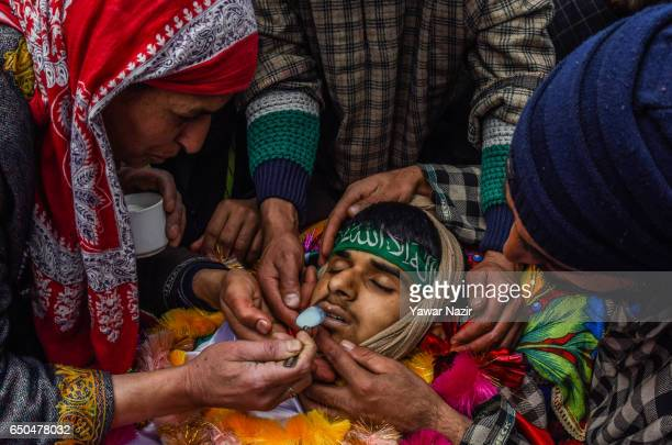 Mother of Amir Nazir a 15 year old teenager who was killed by Indian government forces during clashes in a gun battle offers milk to his dead son...