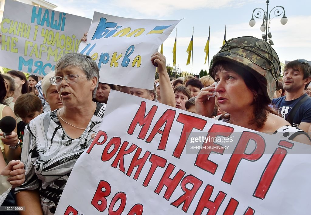 A mother of an Ukrainian serviceman, who is in war with pro-Russian militants in the east of the country, wearing a military helmet, holds a placard reading 'Mothers of Rokytne district plead for help!' as she cries during a rally in front of the presidential office in Kiev on July 16, 2014. Some hundreds of protesters asked to make a rotation of the soldiers and the officers who serve in the east, to provide them with necessary arms, ammunitions and food, to declare martial law and to declare a general mobilization in the country. EU leaders meet today to decide on new sanctions against Russia and pro-Moscow separatists in east Ukraine as Kiev raises fears of an imminent invasion by thousands of Russian troops.