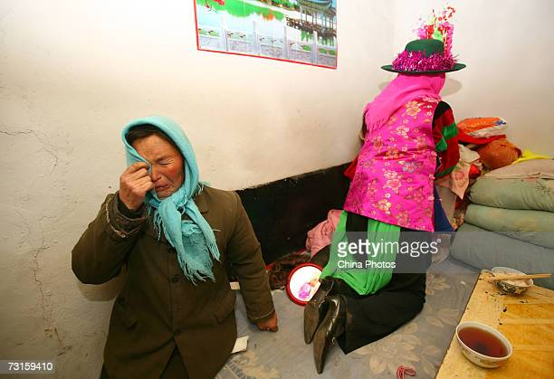 Mother of bride Luo Jinhua cries before her daughter sets out to the groom's home during a Tu ethnic minority group wedding ceremony on January 30...