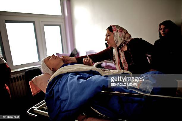 Mother of Iranian breast cancer patient Farvah comforts her after what was meant to be a mastectomy surgery which was turned to a lumpectomy during...