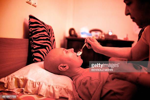 Mother of Iranian breast cancer patient Farvah takes care of her daughter as she feeds her some honey in their house in Tehran on October 18 2013...