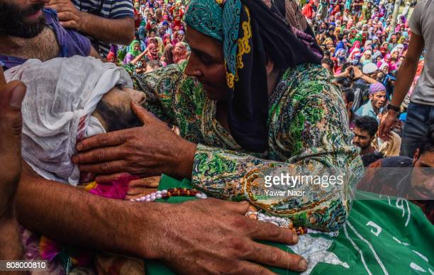Mother of Jahangir Khanday a Kashmiri rebel killed in a gun battle with Indian government forces hugs the body of her son during his funeral on July...