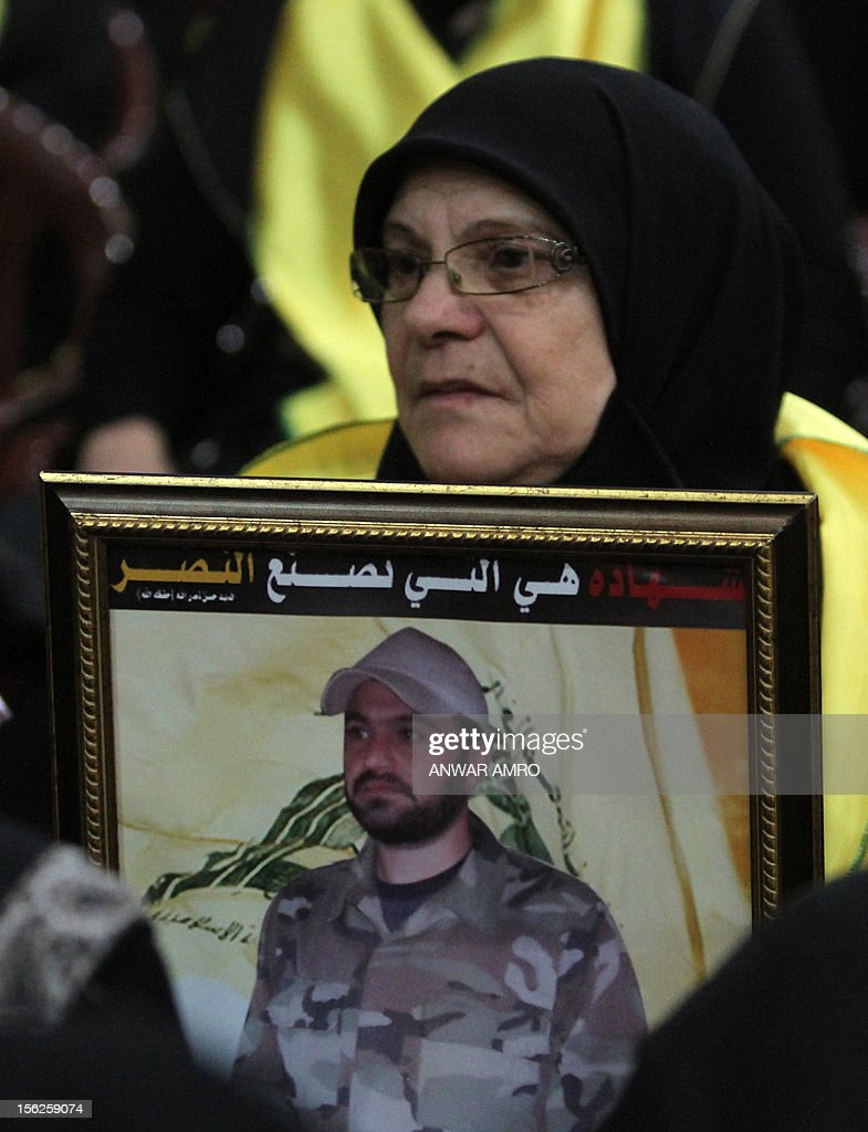 A Mother of killed Hezbollah fighter watches Hezbollah chief Hassan Nasrallah speak during a televised address to a rally marking the party's Martyrs' Day in southern Beirut, on November 12, 2012. Arabic writing on picture reads 'Martyrdom creates victory.' AFP PHOTO/ANWAR AMRO