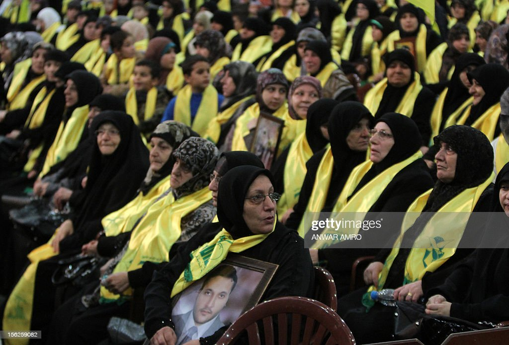 Mother of slain cameraman Ali Shaaban, who worked for local Lebanese station Al-Jadeed prior to his death in April 2012, watches Hezbollah chief Hassan Nasrallah speak during a televised address to a rally marking the party's Martyrs' Day in southern Beirut, on November 12, 2012. AFP PHOTO/ANWAR AMRO