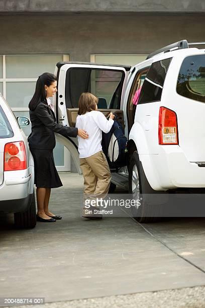 Mother opening car door for son (8-10)