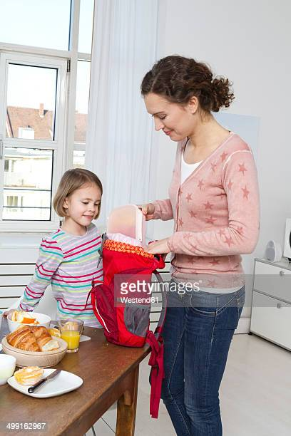 Mother packing daughter's backpack in the morning
