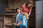 mother putting lunch into sons backpack before school