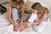 Mother painting daughter's (13-15) toes with nail polish