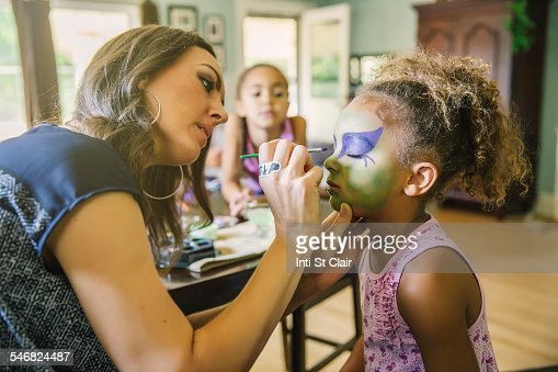 Mother painting face of daughter in living room