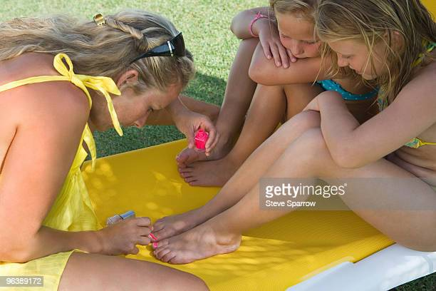 Mother painting toenails of two girls