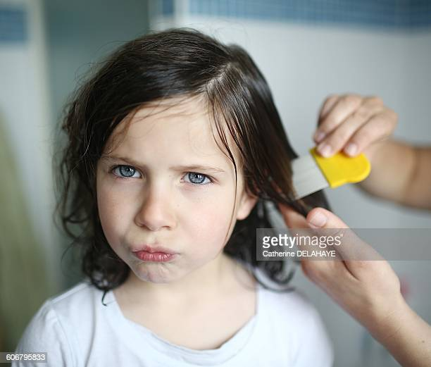 A mother passes a lice comb in the hair of her 6 years old girl