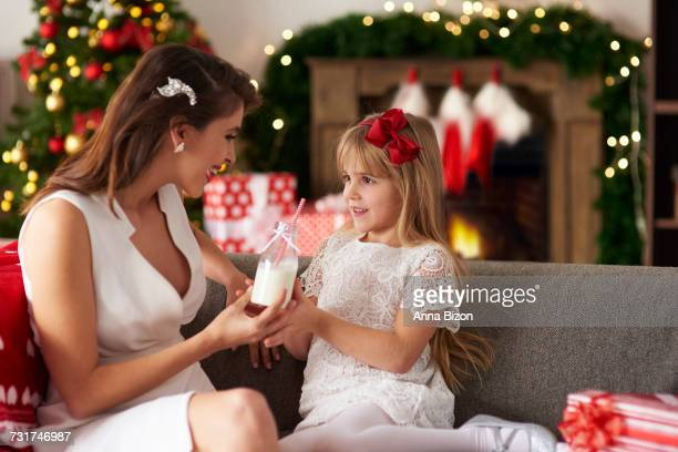 Mother passing bottle of milk to daughter. Debica, Poland