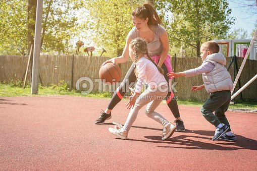 Mother paying basketball wit her children. : Stock Photo