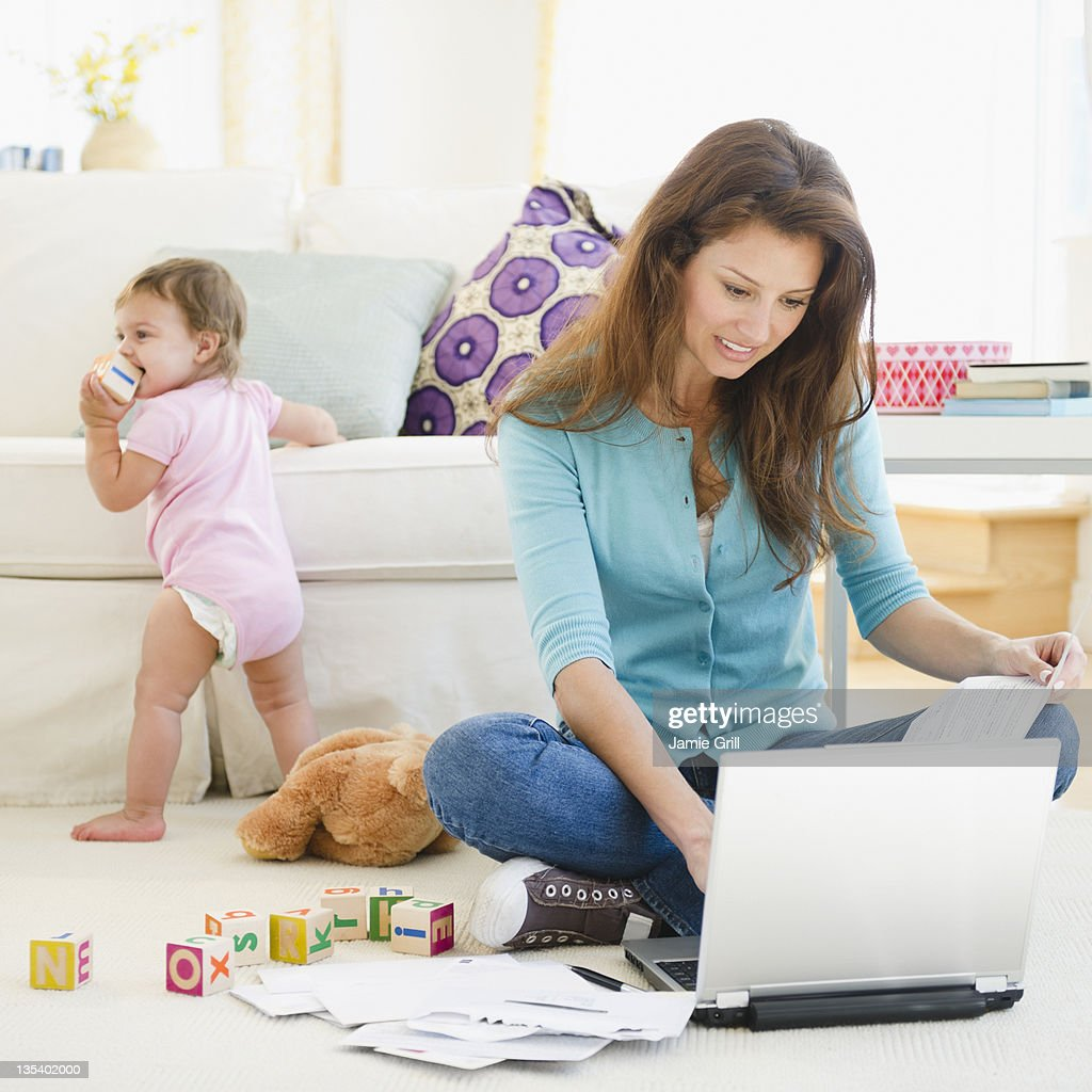 Mother paying bills online, baby in background : Stock Photo