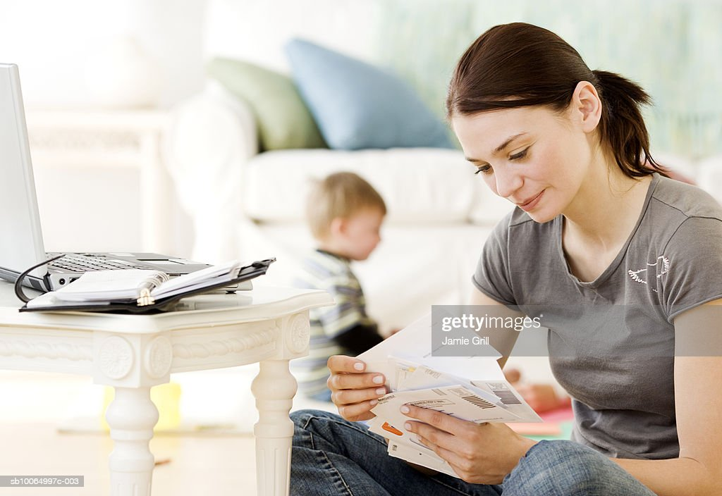 Mother paying bills online, son (21-24 months) playing in background : Stock Photo