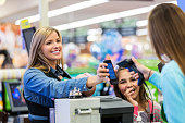 Mid adult Caucasian woman is using her smart phone app to pay for groceries in local grocery store. Employee is scanning smart phone with scanner. Woman is shopping with elementary age daughter and fo