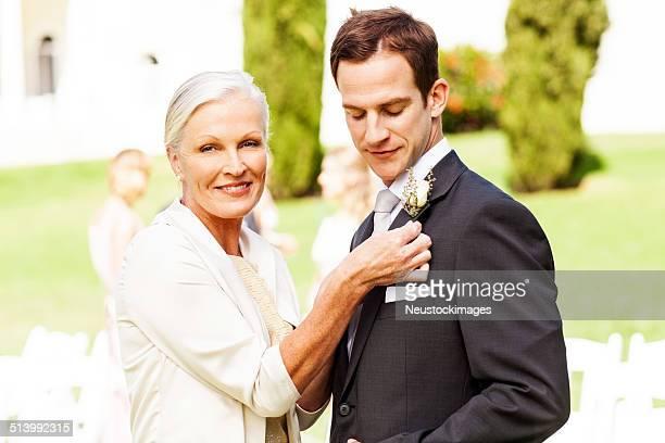 Mère Épingler Petit bouquet porté au vêtement le costume du marié au mariage en plein air