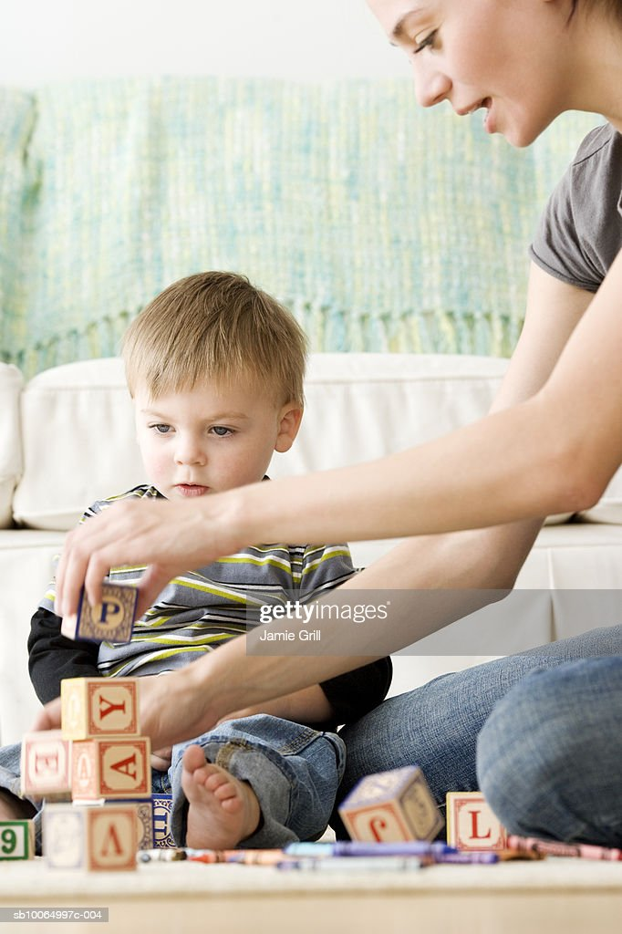 Mother playing alphabet blocks with son (21-24 months) in living room : Stock Photo