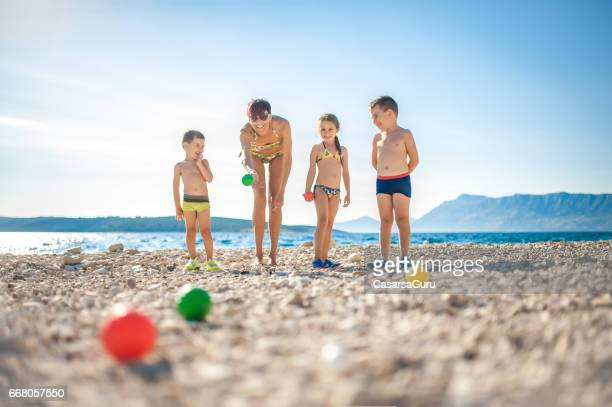 Mother Playing Boccia With Children On The Beach