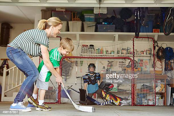 Mother playing hockey in garage with two sons
