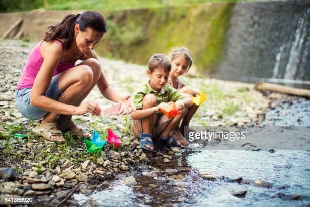 Mère, jouant des bateaux en papier avec ses enfants