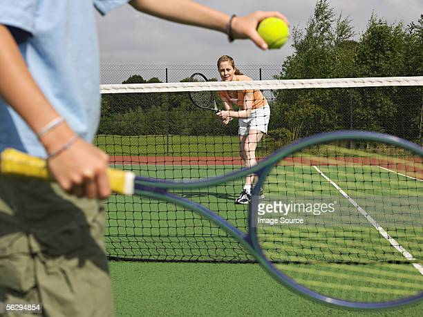 Mother playing tennis with her son