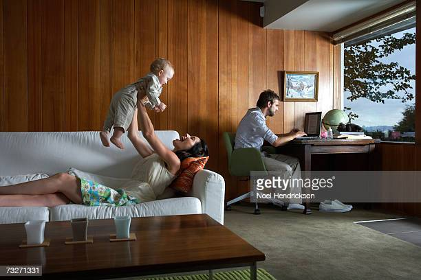 Mother playing with baby girl (6-9 months) while father using laptop in living room