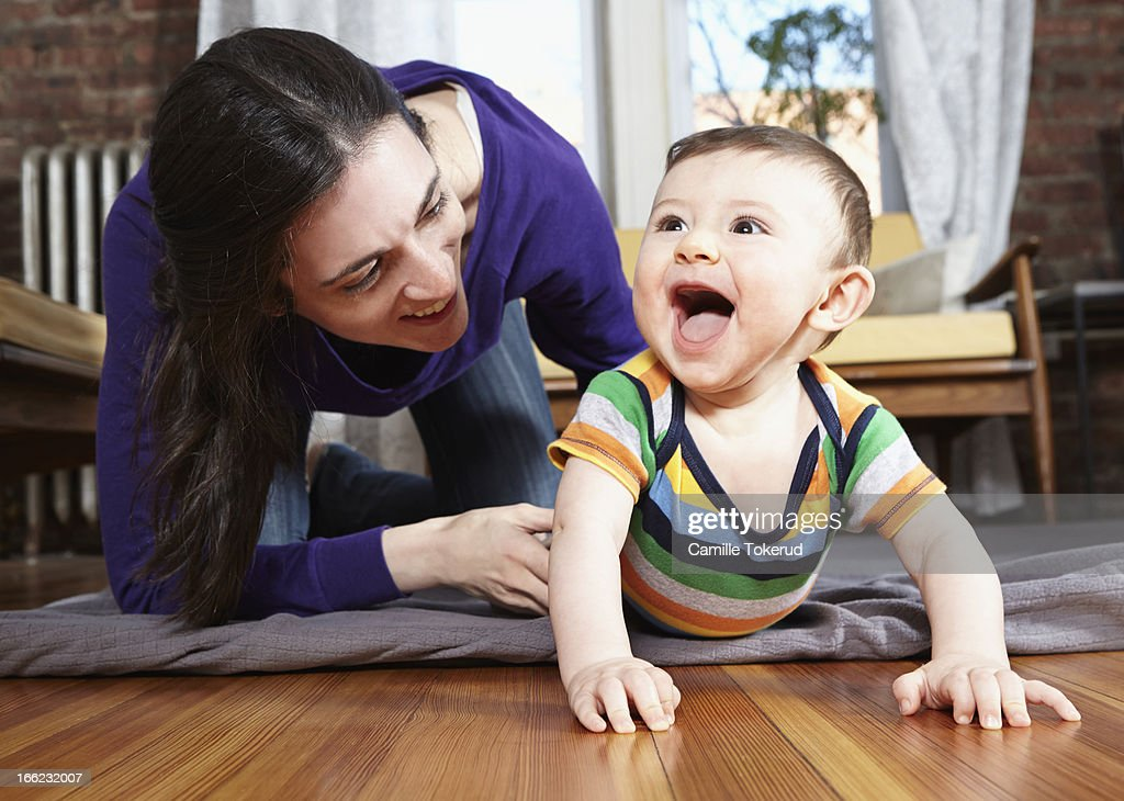 Mother playing with baby on floor : Stock Photo