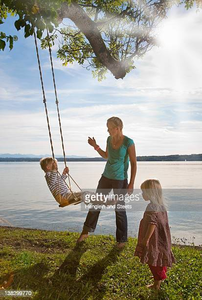 Mother playing with children on swing