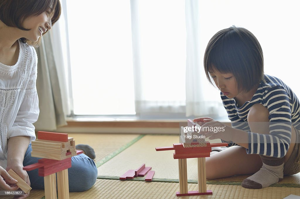 Mother playing with daughter in the room : Stock Photo