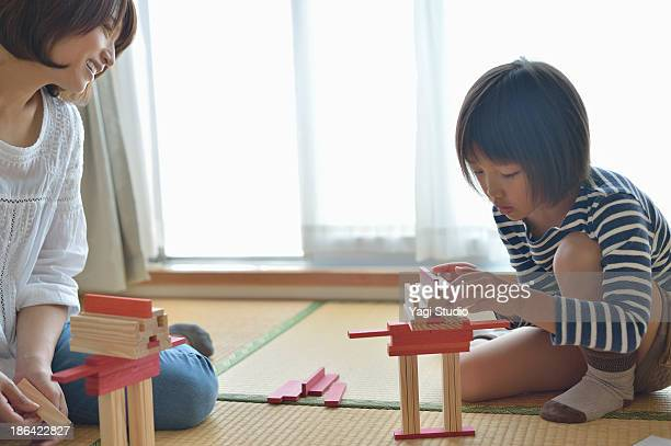 Mother playing with daughter in the room