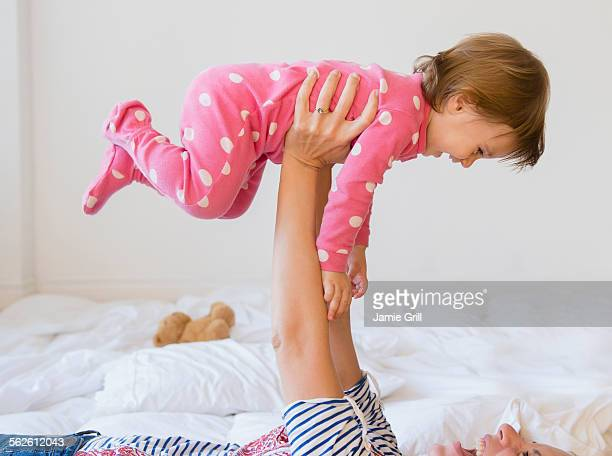 Mother playing with girl (2-3) on bed