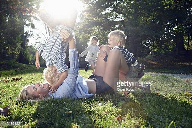 mother playing with her children in a park