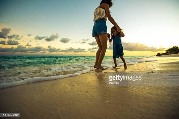 Mãe, a brincar com a menina na praia ao pôr do sol