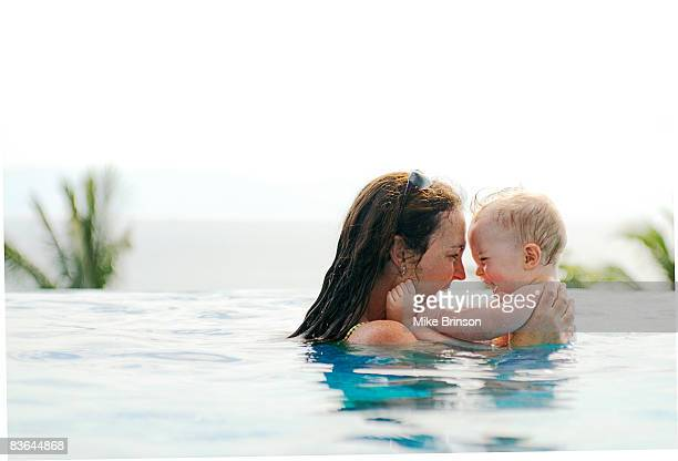 mother playing with toddler in pool