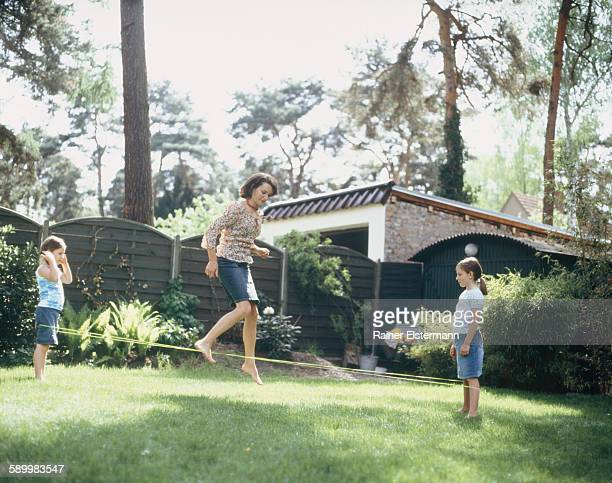 Mother playing with two daughters in garden