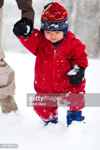 A mother plays with her toddler son in his first big snowstorm in Fort Collins, Colorado.