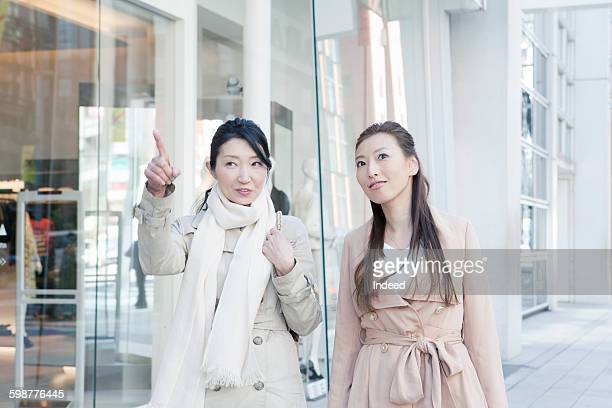 Mother pointing next to daughter on street
