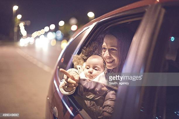 Mother pointing to the baby from the car